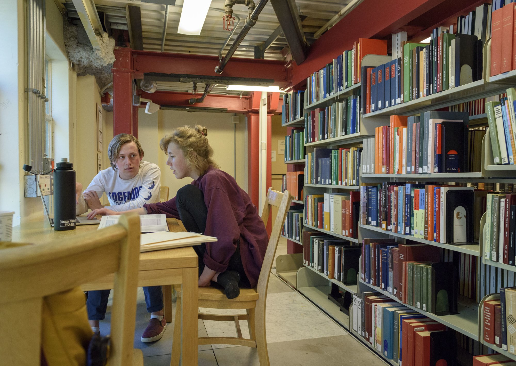Two students are sitting at a desk in a library, talking to each other.