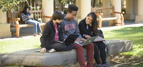 Three students are sitting on a stone bench outside, studying on a sunny day.
