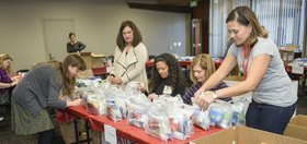 Volunteers assemble toiletry items into care packs